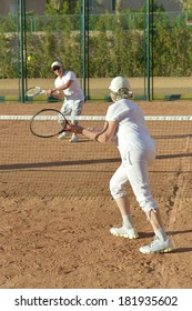 Active elderly couple playing tennis on the court