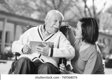Active elderly retired man outdoor reading tablet with asian nurse.