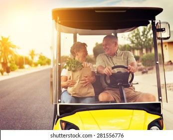 active elderly senior couple getting groceries on golf cart with orange lens flare and warm filter over image. Shot with selective focus.