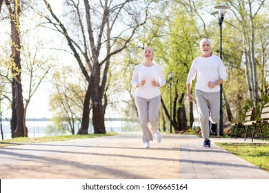 Active exercises. Positive senior couple jogging while being together in the morning