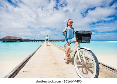 Active family of mother and daughter riding bikes on wooden jetty over tropical ocean enjoying tropical vacation