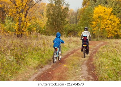 Active family on bikes, cycling outdoors, golden autumn in park, family sport and healthy lifestyle