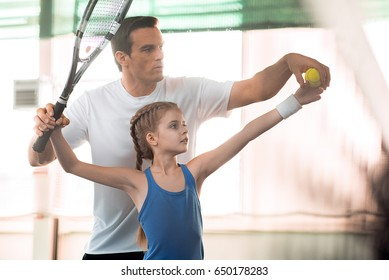 Active family playing tennis on court
