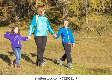 Active family spending time hiking in the colourful woods. Active lifestyle - healthy lifestyle. Children having fun in the meadow, forest in the background.