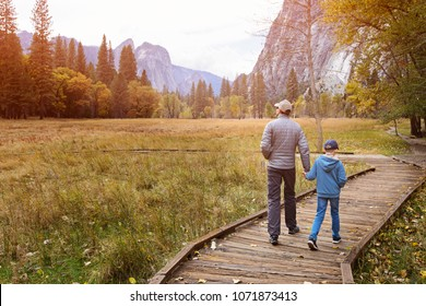 active family of two, father and son, enjoying walking in yosemite national park, california, at autumn