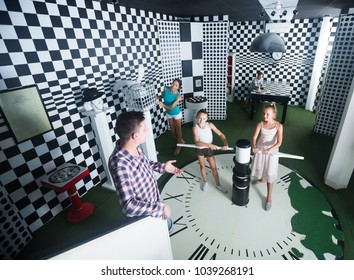 Active family is visiting of escaperoom stylized under chessboard