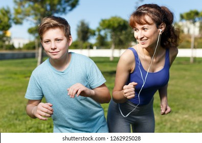 Active family of young mother and tweenage son running together on sports ground and listening music