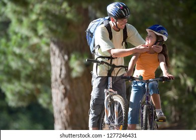 Active father and daughter mountain biking in forest fastening helmet