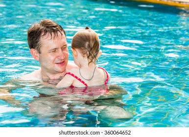 Active father teaching his toddler daughter to swim in pool on tropical resort. Summer vacations and sport  concept