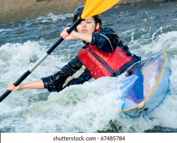 active female kayaker with an oar on the water