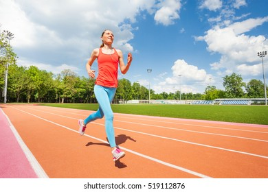 Active female runner working out at stadiums track