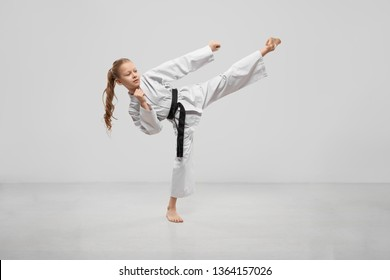 Active female teenager practising karate in studio. Sporty child wearing kimono kicking with leg in studio. Concentrated girl fighting and training. Concept of martial atrs and sport.