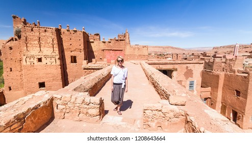 Active female traveler on travel at Ait Benhaddou,fortified city, kasbah or ksar, along the former caravan route between Sahara and Marrakesh in present day Morocco.