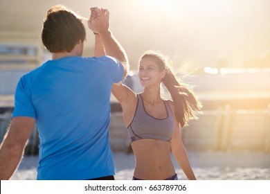 Active fit friends couple high five in celebration after completing their gruelling exercise workout run, golden sun flare behind