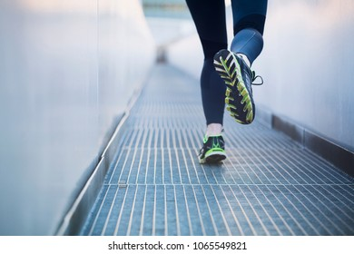 An active fit woman running in an urban environment. Shallow DOF, focus on the back shoe.