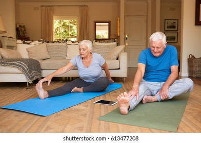 Active and focused senior couple doing the stretching while practicing yoga together in their living room at home