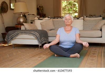 Active and focused senior woman sitting in the lotus pose and meditating while practicing yoga alone in her living room at home