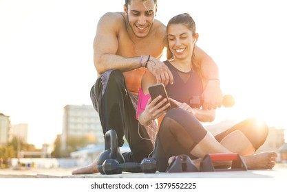 Active friends training while checking on the phone the exercises of their sport session. The personal trainer smiling together with a sportiv girl, satisfacted of their calisthenics training.