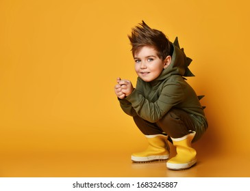 Active and frolic kid boy in hoodie with dinosaurus spikes at his back and cowl and in yellow rubber boots wellies is sitting squatting free copy space