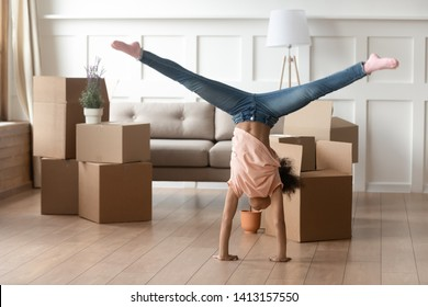 Active funny african american kid doing cartwheel in living room on moving day, cute little black child girl playing on floor with cardboard boxes in new modern house celebrate relocation renovation