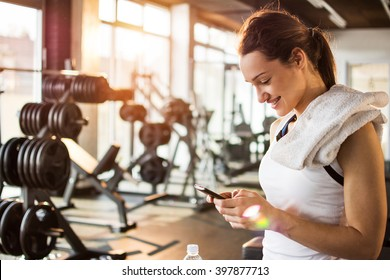 Active girl with smartphone listening to music in gym.