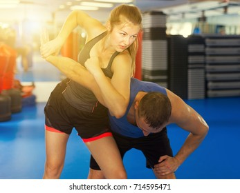 Active girl with trainer are training captures on the self-defense course in gym