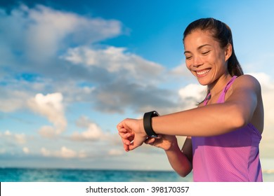 Active girl using fitness tracker smart watch jogging on summer nature outdoors looking at health data during sports activity touching the screen of her smartwatch.