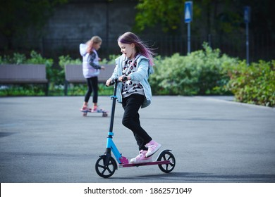 Active girls riding kick scooter and skateboard in skate park. Children having free time playing. The concept of a healthy lifestyle. Kids sport.