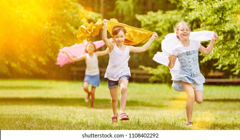 Active girls run cheerful in the park in summer