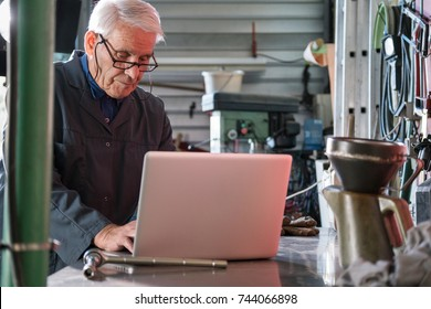An active gray-haired senior working in his studio, checking something on his laptop.