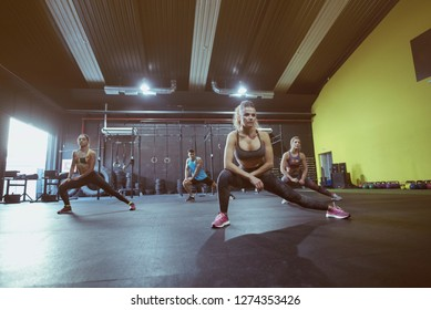 Active group of people training in sport dance class, mature woman teaching