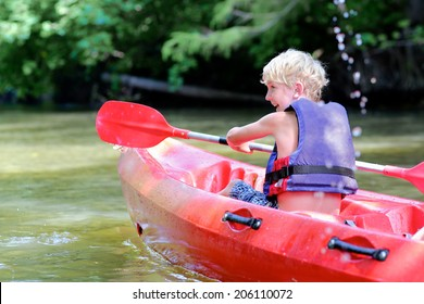 Active happy child, teenage school boy, having fun enjoying adventurous experience kayaking on the river on a sunny day during summer vacation