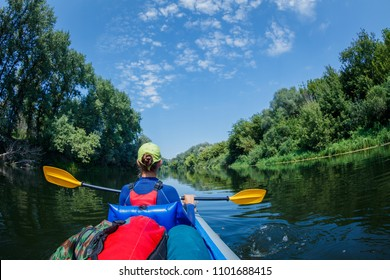 Active happy family. Back view of Girl having fun and enjoying adventurous experience kayaking on the river on a sunny day during summer vacation