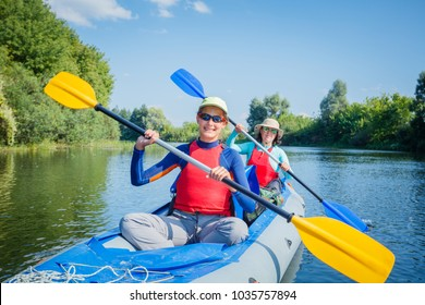 Active happy family. Girl with her mother having fun together enjoying adventurous experience kayaking on the river on a sunny day during summer vacation