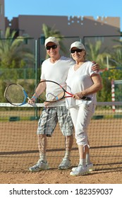 Active happy senior couple playing tennis outdoors