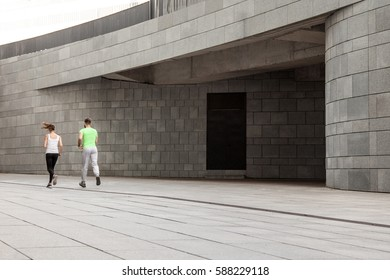 Active happy young couple jogging side by side in an urban street during their daily workout in a health and fitness concept
