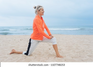 Active healthy blond woman doing stretching exercises on a sandy tropical beach on a hazy day in a close up profile view