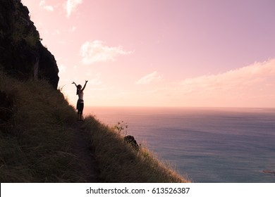 Active healthy lifestyle concept.  Happy female hiker standing on a cliff with her arms up in the air feeling free