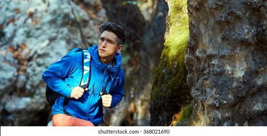 Active healthy man hiking in beautiful autumn forest. Portrait of happy smiling young man resting of forest clearing during hike holidays.