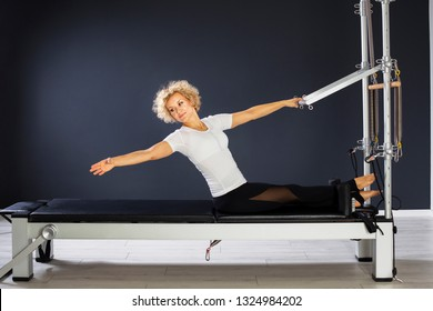 Active and healthy woman exercising on stretching machine