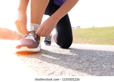 Active healthy woman tying running shoes,  jogging runner healthcare and well being concept