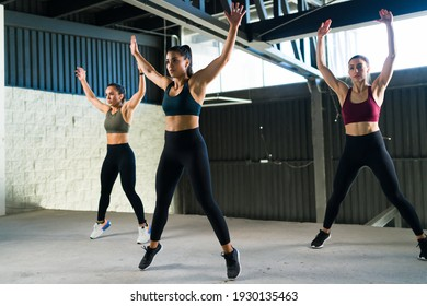 Active and healthy women doing jumping jacks during a HIIT class. Three beautiful and fit women working out at the gym with power training