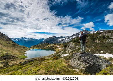 Active hiker with backpack in Pyrenees overlooking lake Tristaina in Andorra
