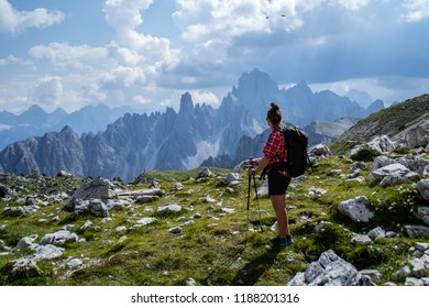 Active hiker tourist young woman walking/hiking Tre Cime di Lavaredo trail in Dolomites, Italy, Europe. Beautiful mountain scenic landscape view. Summer outdoor activity or active holiday concept.