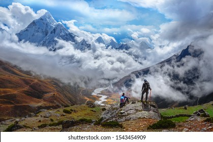 Active hikers hiking, enjoying the view, looking at Himalaya mountains landscape.Tracking to Everest base camp valley with Ama Dablam view. Travel sport lifestyle concept