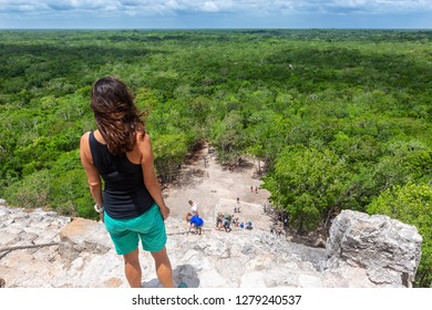 Active hiking traveler woman looks down the steep steps of the Nohoch Mul pyramid in Coba, Yucatan, Mexico