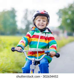 Active kid boy in red safety helmet driving on his first bicycle on summer day. Active leisure for children outdoors.