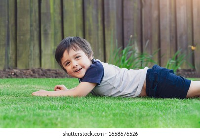 Active kid having fun lying down on green  grass in the garden. Healthy Child boy laying on lawn Relaxation happy childhood enjoying summer day concept