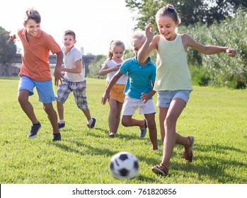 active kids having fun and kicking football in park on summer day  together