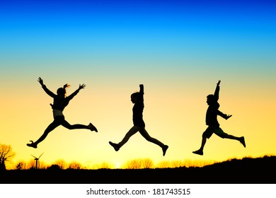 Active kids jump in meadow at sunset